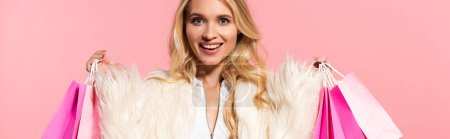 Photo for Happy beautiful blonde woman in white faux fur jacket holding shopping bags isolated on pink, panoramic shot - Royalty Free Image