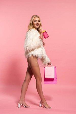 Photo pour Vue latérale de heureuse femme blonde sexy en body blanc et veste en fausse fourrure tenant boissons et sacs à provisions sur rose - image libre de droit