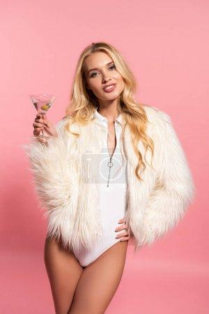 Photo pour Heureuse belle femme blonde en body blanc et veste en fausse fourrure tenant un verre de cocktail à la main sur la hanche isolée sur rose - image libre de droit