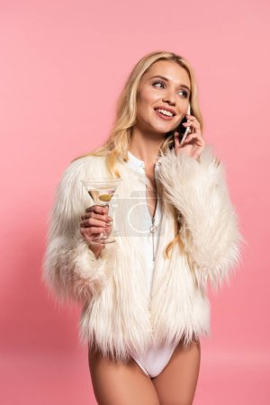 Photo for Happy beautiful blonde woman in white bodysuit and faux fur jacket holding glass of cocktail and talking on smartphone isolated on pink - Royalty Free Image