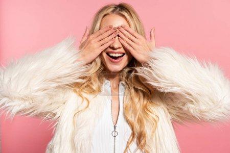 Foto de Feliz hermosa mujer rubia en chaqueta de piel sintética blanca con las manos en los ojos aislados en rosa - Imagen libre de derechos