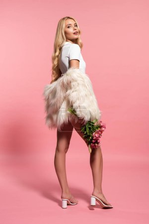 sexy blonde woman in white faux fur jacket and bodysuit holding flowers isolated on pink
