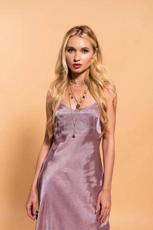 Photo pour Élégante femme blonde en robe de satin violet et collier posant isolé sur beige - image libre de droit