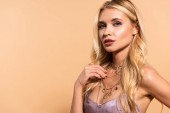 "Постер, картина, фотообои ""elegant blonde woman in violet satin dress touching necklace isolated on beige"""