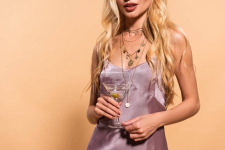 Photo for Partial view of elegant blonde woman in violet satin dress and necklace holding cocktail isolated on beige - Royalty Free Image