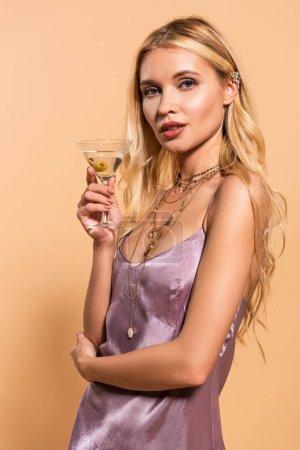Photo pour Femme blonde élégante dans la robe et le collier violet satin retenant le cocktail d'isolement sur le beige - image libre de droit