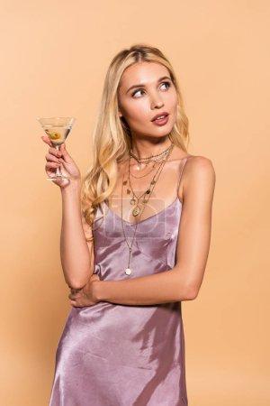 Photo pour Femme blonde élégante rêveuse dans la robe et le collier violets de satin retenant le cocktail d'isolement sur le beige - image libre de droit