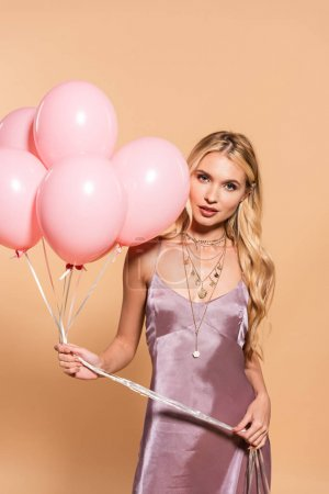 Photo for Elegant blonde woman in violet satin dress and necklace holding pink balloons on beige - Royalty Free Image