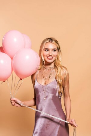 Photo for Happy elegant blonde woman in violet satin dress and necklace holding pink balloons  on beige - Royalty Free Image