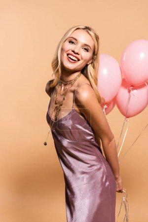 Photo pour Femme blonde heureuse dans la robe et le collier violets de satin retenant des ballons roses sur le beige - image libre de droit