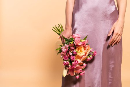 Photo for Partial view of elegant woman in violet satin dress holding bouquet of flowers isolated on beige - Royalty Free Image
