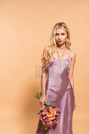 Photo pour Élégante femme en robe de satin violet et collier tenant bouquet de fleurs isolées sur beige - image libre de droit