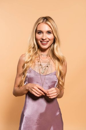Foto de Smiling elegant blonde woman in violet satin dress and necklace posing isolated on beige - Imagen libre de derechos