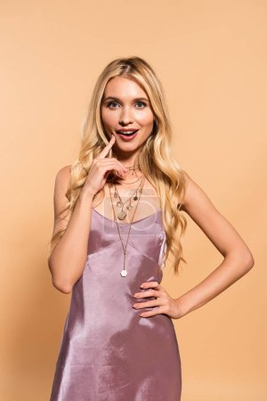 Photo for Happy elegant blonde woman in violet satin dress and necklace posing with hand on hip on beige - Royalty Free Image