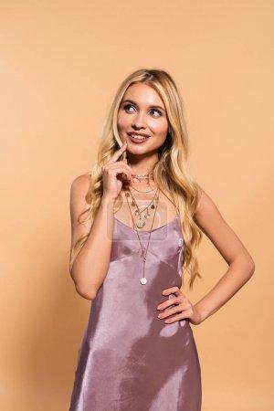 Photo pour Femme blonde élégante rêveuse dans la robe et le collier de satin violet posant sur le beige - image libre de droit