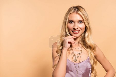 Photo for Smiling blonde woman in violet dress and necklace isolated on beige - Royalty Free Image