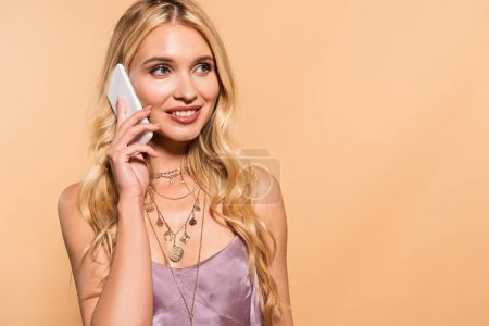 Photo for Smiling elegant blonde woman in violet satin dress and necklace talking on smartphone isolated on beige - Royalty Free Image