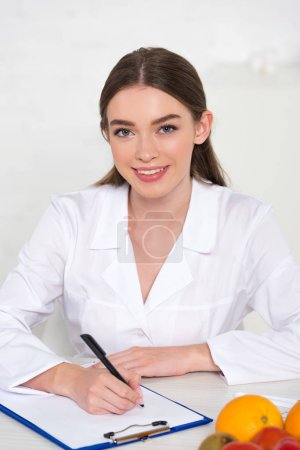 Photo for Smiling dietitian in white coat at workplace writing in clipboard with fruits on table - Royalty Free Image