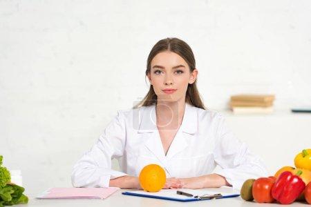 Photo pour Vue avant de la diététiste dans le manteau blanc au lieu de travail avec des légumes, le dossier et le presse-papiers sur la table - image libre de droit