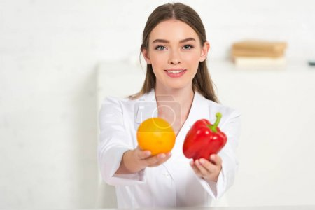 Photo for Front view of smiling dietitian in white coat holding orange and red bell pepper - Royalty Free Image