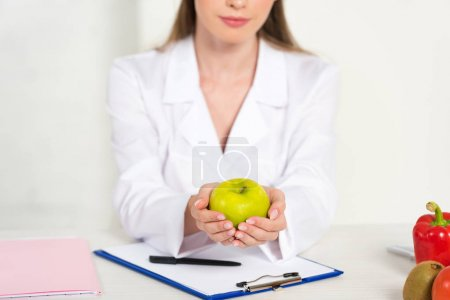 Photo for Partial view of dietitian in white coat holding apple at workplace - Royalty Free Image