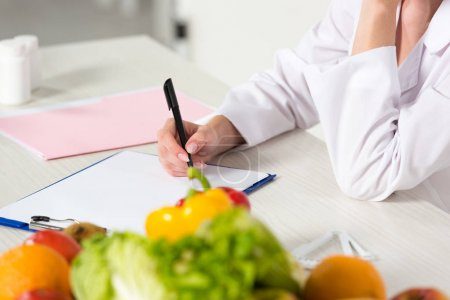 Photo for Partial view of dietitian in white coat writing in clipboard at workplace with fruits and vegetables on table - Royalty Free Image