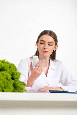 Photo pour Diététiste coûteux en manteau blanc tenant des pilules sur le lieu de travail - image libre de droit