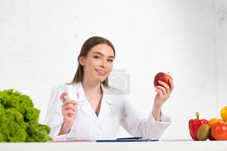 Photo pour Diététiste souriant en manteau blanc tenant des pilules et de la pomme sur le lieu de travail - image libre de droit