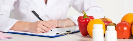 Photo for Panoramic shot of dietitian in white coat writing in clipboard at workplace with pills, fruits and vegetables on table - Royalty Free Image