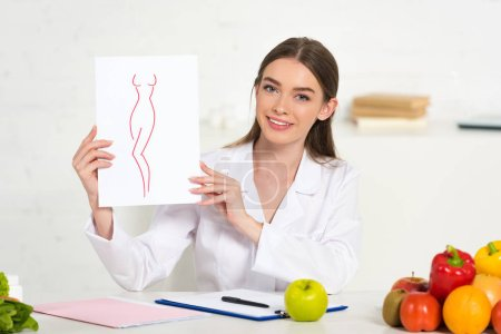 Photo for Smiling dietitian in white coat holding paper with image of perfect body at workplace with fruits and vegetables on table - Royalty Free Image
