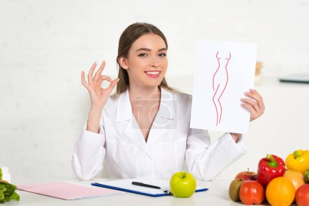 Photo for Smiling dietitian in white coat holding paper with image of perfect body and showing okay sign at workplace with fruits and vegetables on table - Royalty Free Image