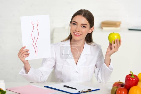 Photo for Smiling dietitian in white coat holding paper with image of perfect body and apple at workplace with fruits and vegetables on table - Royalty Free Image