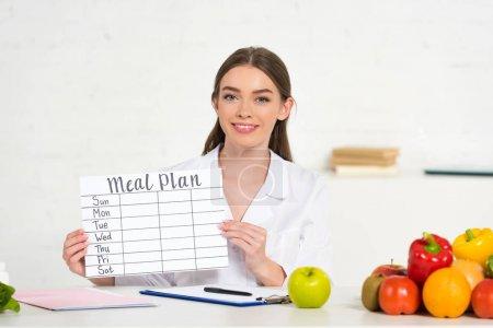 Foto de Vista frontal de dietista sonriente en bata blanca sosteniendo plan de comidas en el lugar de trabajo con frutas y verduras en la mesa - Imagen libre de derechos