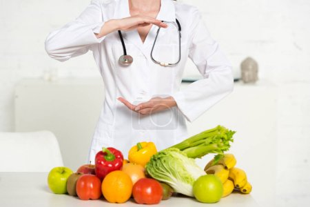 Photo for Partial view of dietitian in white coat with stethoscope near fresh fruits and vegetables - Royalty Free Image