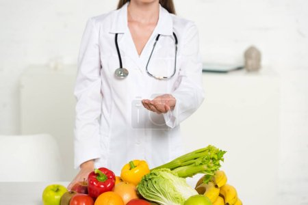 Photo for Cropped view of dietitian in white coat with stethoscope standing with outstretched hand near fresh fruits and vegetables - Royalty Free Image