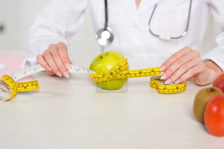Photo for Cropped view of dietitian in white coat holding measure tape at table with fruits - Royalty Free Image