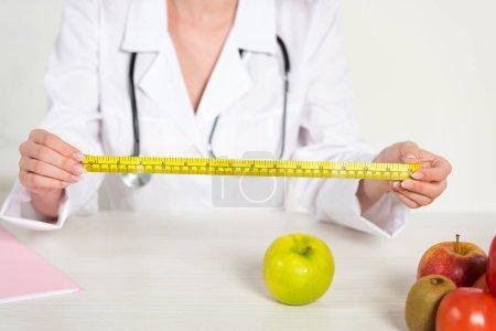 Foto de Vista recortada de dietista en manto blanco sosteniendo cinta métrica y alimentos frescos en la mesa - Imagen libre de derechos