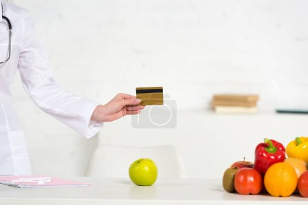 Photo for Cropped view of dietitian in white coat holding credit card near table with fresh fruits and vegetables - Royalty Free Image