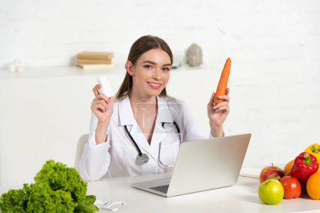 Photo for Smiling dietitian in white coat holding pills and carrot near laptop - Royalty Free Image