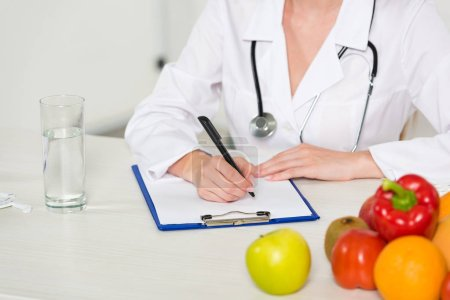 Photo for Cropped view of dietitian in white coat writing in clipboard at workplace - Royalty Free Image