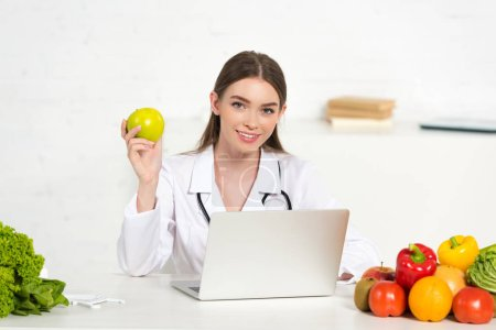 Photo for Smiling dietitian in white coat holding apple at workplace with laptop - Royalty Free Image
