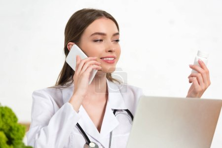 Photo pour Médecin souriant en manteau blanc tenant des pilules et parlant sur smartphone - image libre de droit