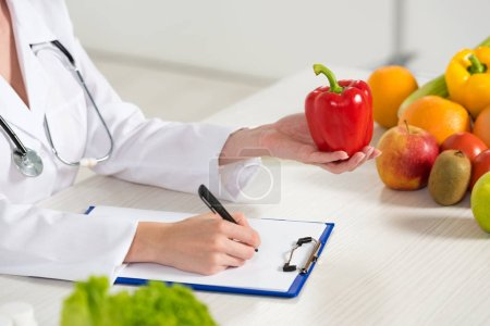 Photo for Partial view of dietitian in white coat holding red bell pepper and writing in clipboard at workplace - Royalty Free Image