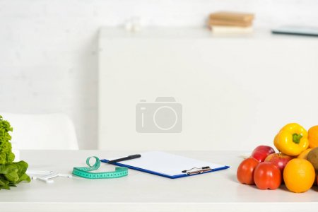 Photo for Clipboard with pen, measure tape and fresh fruits and vegetables on table - Royalty Free Image