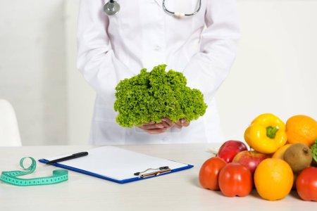 Photo pour Vue recadrée de la diététiste en manteau blanc tenant de la laitue sur le lieu de travail - image libre de droit