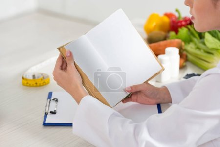 Photo for Cropped view of dietitian in white coat reading book at workplace - Royalty Free Image