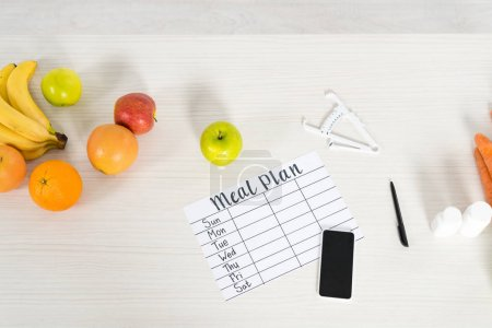 Photo for Top view of meal plan, smartphone with blank screen, caliper, pills and fresh fruits on wooden surface - Royalty Free Image