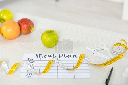 Photo pour Plan de repas, ruban à mesurer, étrier, stylo et fruits frais sur surface en bois - image libre de droit