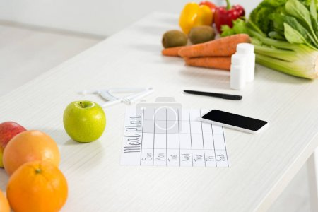 Photo for Meal plan, smartphone with blank screen, pills, pen, caliper, fresh fruits and vegetables on table - Royalty Free Image