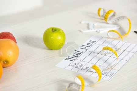 meal plan, caliper, measure tape and fresh fruits on table